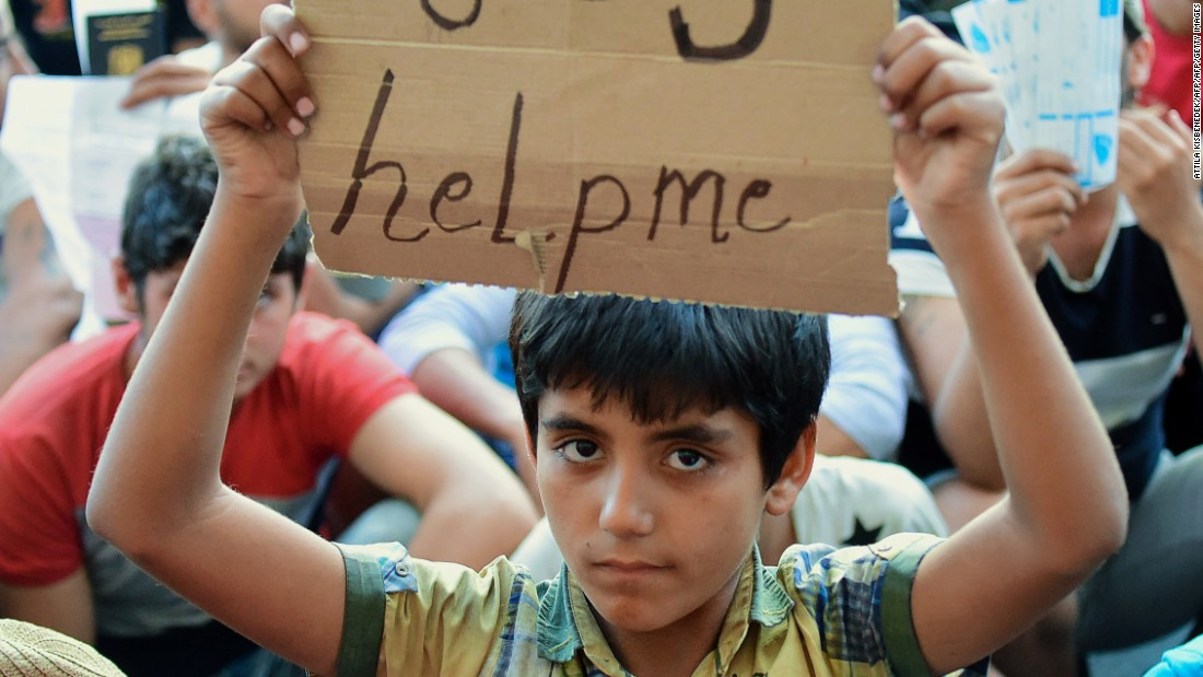 "A boy holds a sign reading ""SOS help me"" in front of Keleti station."
