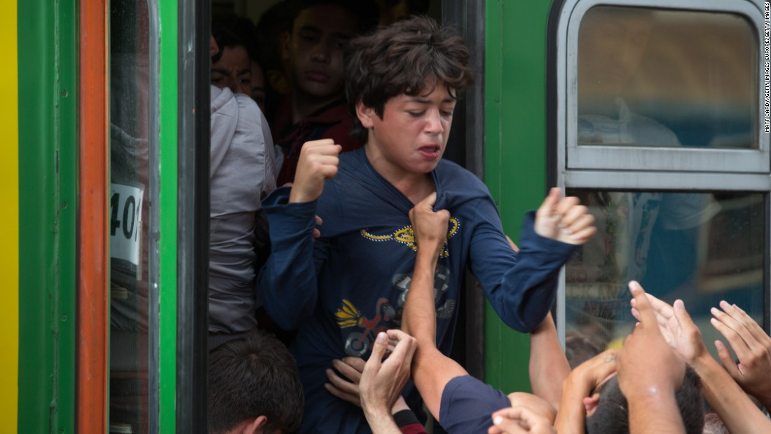 Migrants clamor at the doors of a train carriage in Keleti station.