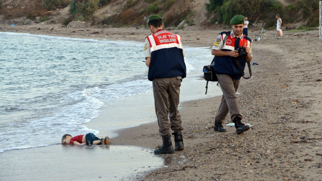 """Authorities stand near the lifeless body of 2-year-old Aylan Kurdi on the shore of Bodrum, Turkey, on Wednesday, September 2. Aylan, his brother Galip and their mother <a href=""""http://ift.tt/1iCx2E5; target=""""_blank"""">drowned while fleeing Syria</a>. This photo has been shared widely around the world, often with a Turkish hashtag that means """"Flotsam of Humanity."""""""