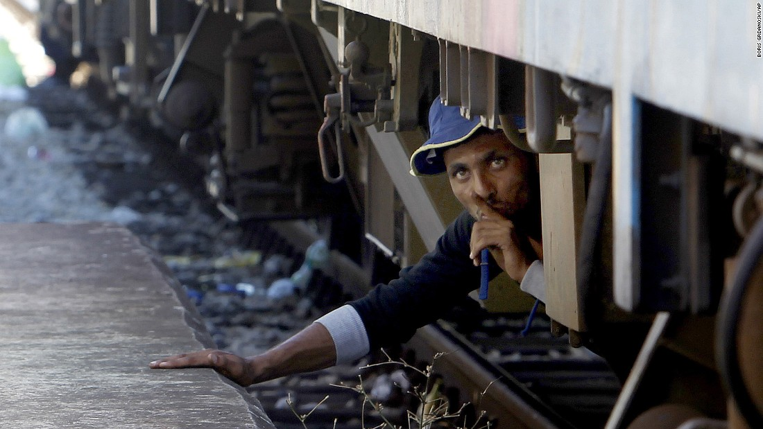 A migrant in Gevgelija, Macedonia, tries to sneak onto a train bound for Serbia on Monday, August 17.