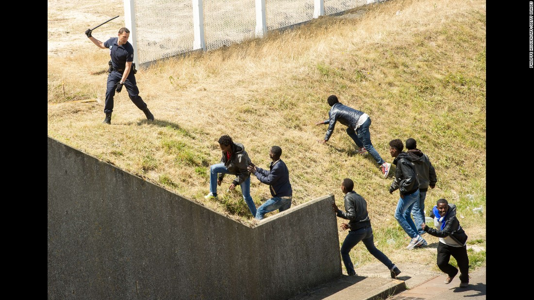 A police officer in the northern French city of Calais tries to prevent migrants from heading for the Channel Tunnel to England on Wednesday, June 17.