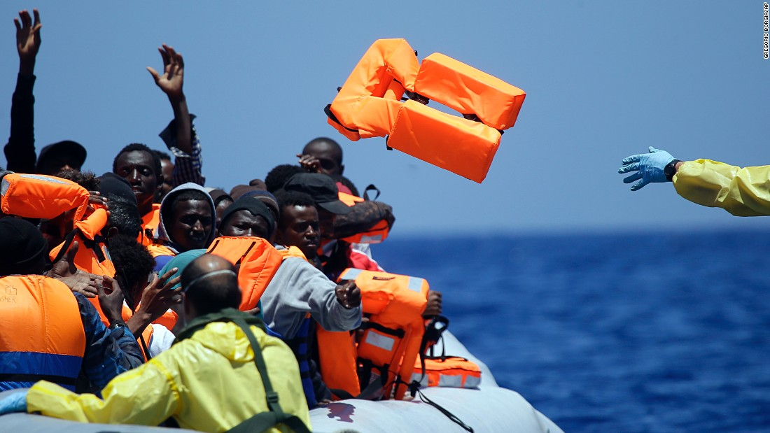 A Belgian sailor throws life vests to refugees during a search-and-rescue mission off the Libyan coast on Tuesday, June 23.