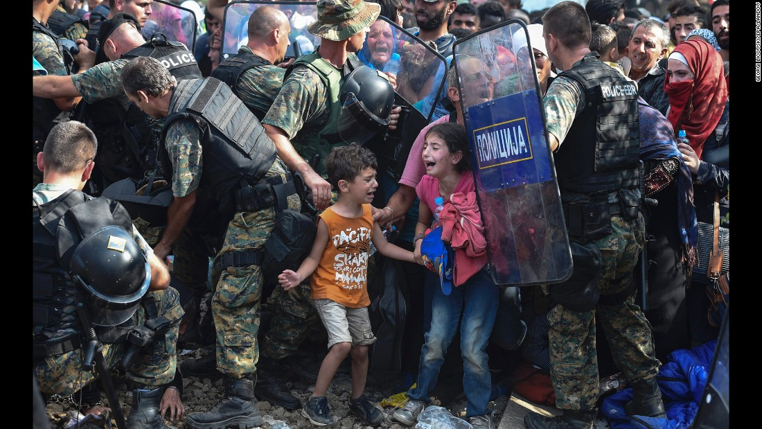 "Children cry as migrants in Greece try to break through a police cordon to cross into Macedonia on Friday, August 21. Thousands of migrants -- most of them fleeing Syria's bitter conflict -- were stranded in a <a href=""http://www.cnn.com/2015/08/22/europe/europe-macedonia-migrant-crisis/"" target=""_blank"">no-man's land</a> on the border."
