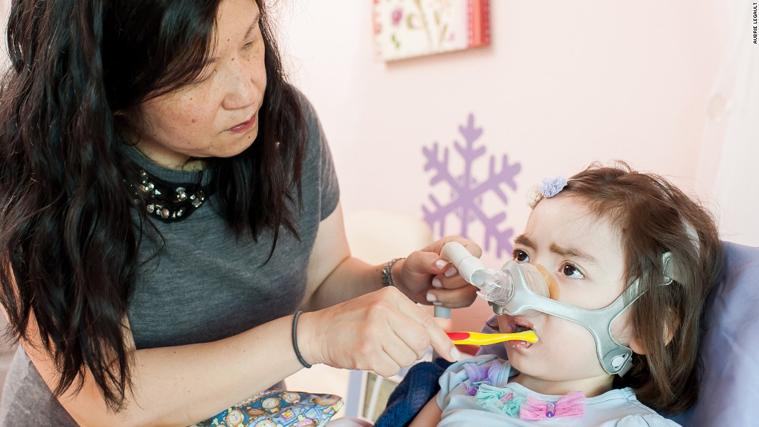Julianna, who has Charcot-Marie-Tooth disease, once had nearly full use of her arms, but now can't even hold a small toy without help. Her mother, Michelle Moon, brushes her teeth.