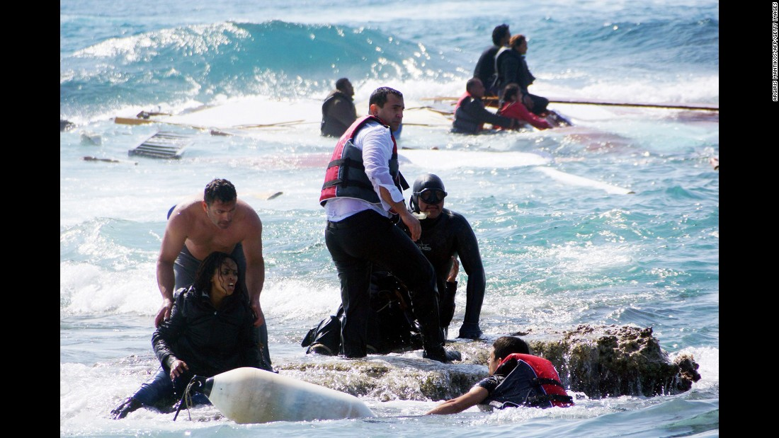 Local residents and rescue workers help migrants from the sea after a boat carrying them sank off the island of Rhodes, Greece, on Monday, April 20.