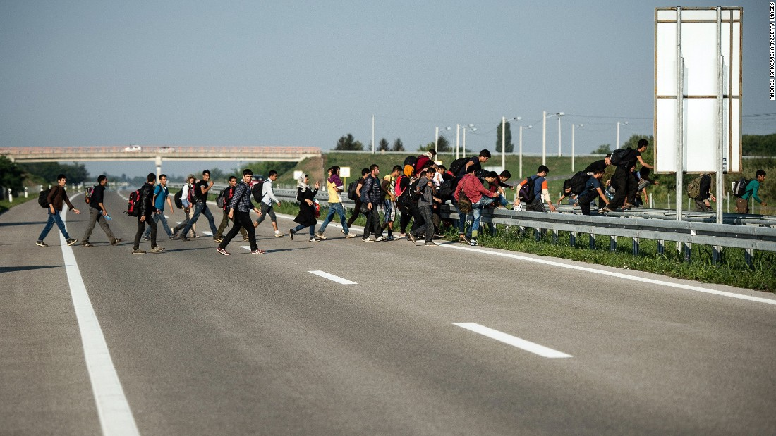 Refugees cross a highway near Horgos, Serbia, toward the Hungarian border on Friday, August 28.