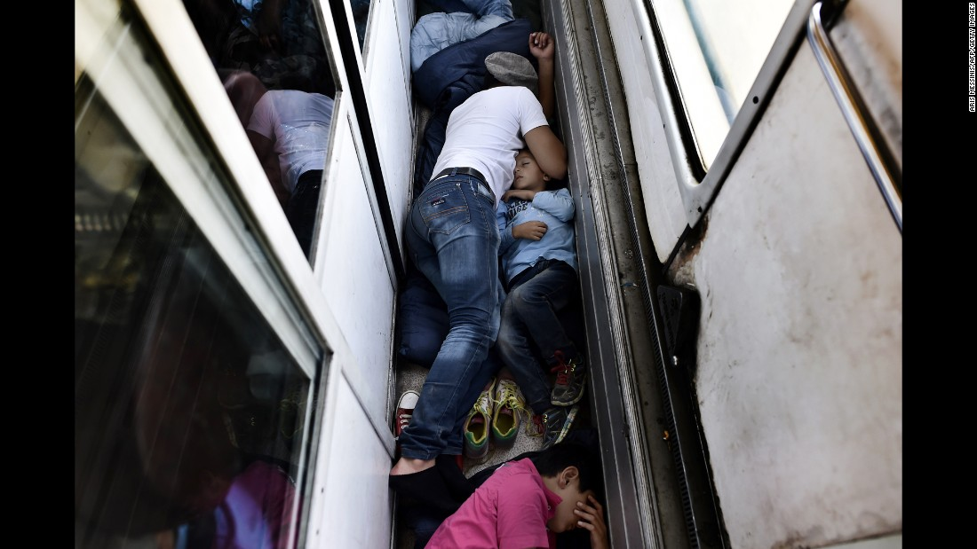 Syrian refugees sleep on the floor of a train car taking them from Macedonia to the Serbian border on Sunday, August 30.