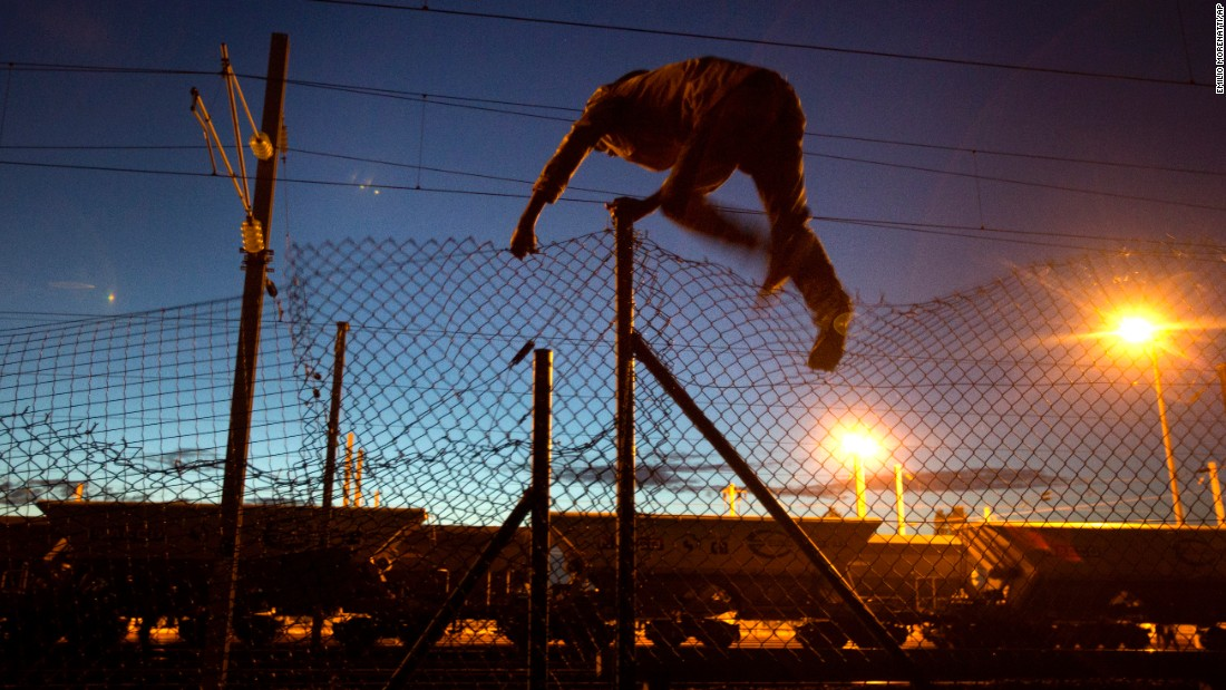 A migrant jumps a fence in Calais, France, as he attempts to access the Channel Tunnel leading to England on August 5.