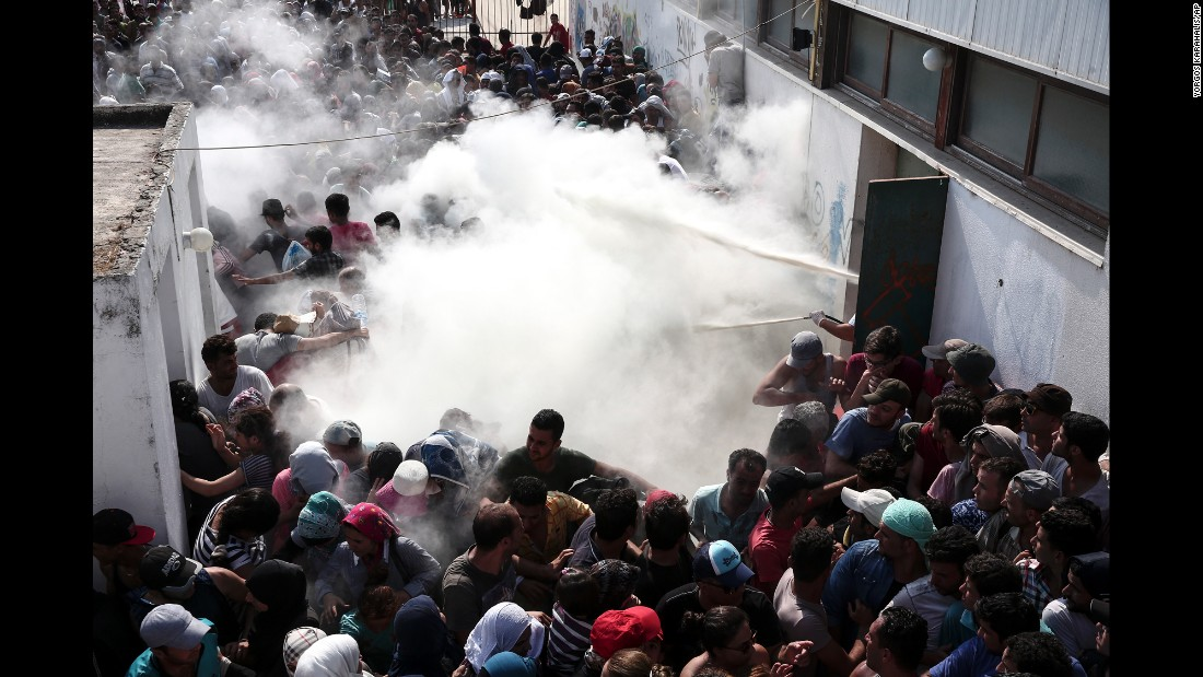 Policemen try to disperse hundreds of migrants by spraying them with fire extinguishers during a registration procedure in Kos, Greece, on Tuesday, August 11.