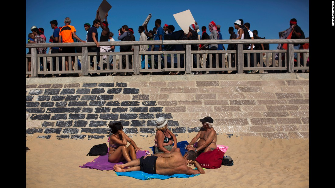 Refugees walk past people on a beach in Calais, France, during a demonstration on Saturday, August 8.