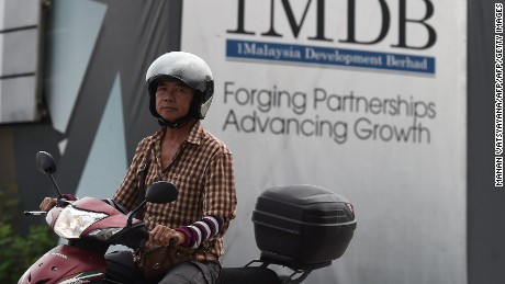 A motorist rides past a hoarding at the construction site of the 1 Malaysia Development Berhad (1MDB) flagship Tun Razak Exchange in Kuala Lumpur on July 8, 2015. A government task force investigating a Malaysian state-owned investment fund seized documents from its offices on July 8 after a probe allegedly found hundreds of millions of dollars in the prime minister's personal bank accounts. AFP PHOTO / MANAN VATSYAYANA