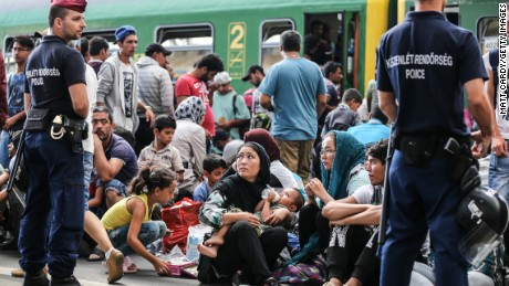 Police stand guard as migrants sit on the platform of Keleti station after it was reopened this morning in central Budapest on September 3, 2015 in Budapest, Hungary. Although the station has reopened all international trains to Western Europe have bee cancelled. According to the Hungarian authorities a record number of migrants from many parts of the Middle East, Africa and Asia are crossing the border from Serbia. Since the beginning of 2015 the number of migrants using the so-called Balkans route has exploded with migrants arriving in Greece from Turkey and then travelling on through Macedonia and Serbia before entering the EU via Hungary. The massive increase, said to be the largest migration of people since World War II, led Hungarian Prime Minister Victor Orban to order Hungary's army to build a steel and barbed wire security barrier along its entire border with Serbia, after more than 100,000 asylum seekers from a variety of countries and war zones entered the country so far this year.