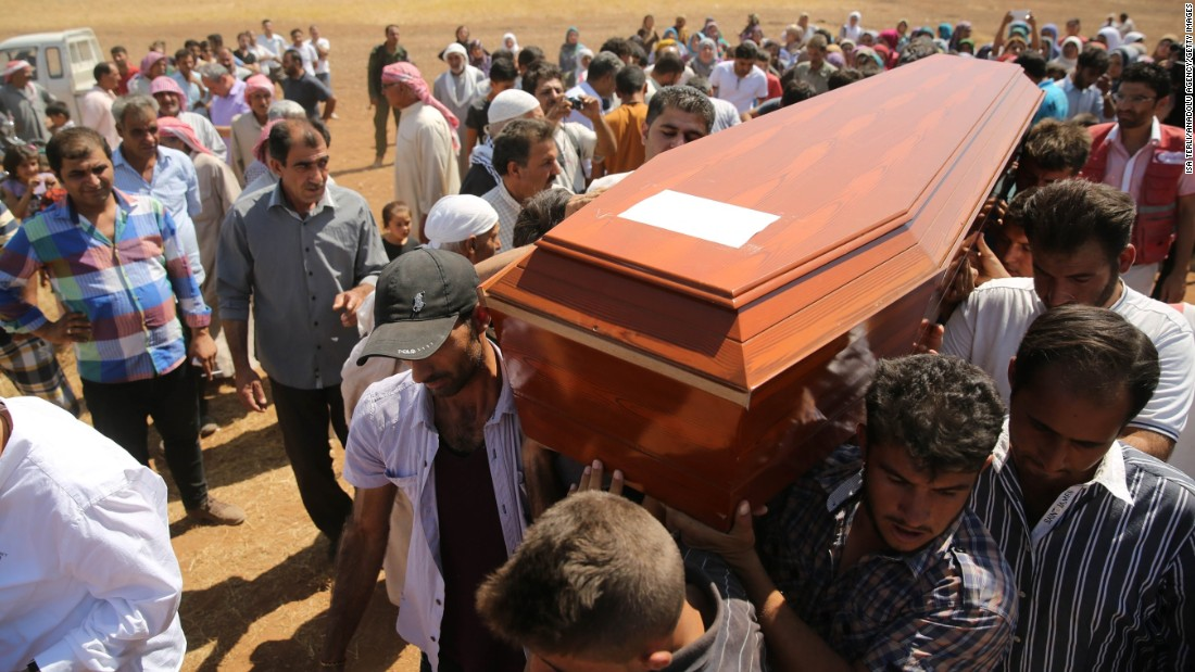 People carry a coffin during the funeral for Aylan, Galip and the boys' mother, Rehen, in Kobani, Syria, on Friday, September 4. Aylan's father brought their bodies back from Turkey for burial in the city they had fled.