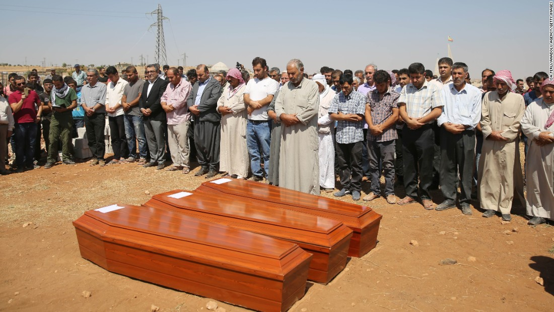 People stand near the coffins during the burial ceremony in Kobani on September 4.