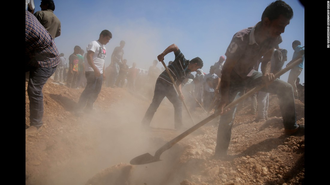 Men dig graves for the three coffins in Kobani on September 4.