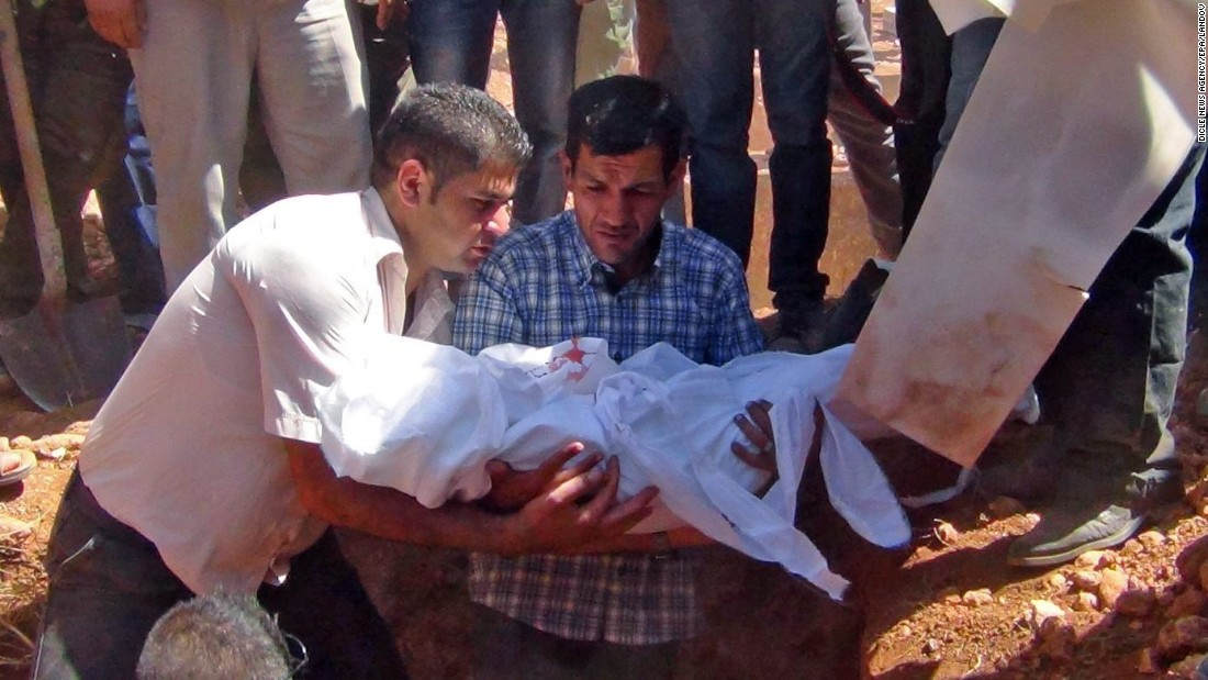 Kurdi holds Aylan's body before burying him in Kobani on September 4.