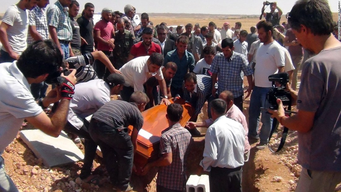 One of the coffins gets lowered into the ground September 4 in Kobani.