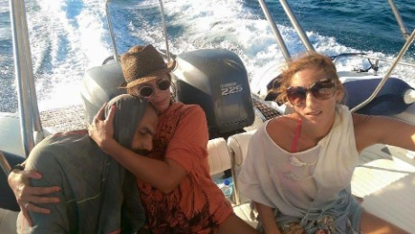Sandra Tsiligeridou (C) cradles Syrian refugee Mohammed Besmar after rescuing him from the Aegean Sea.