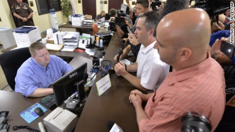 Rowan County deputy clerk Brian Mason, left, takes the information from James Yates, and his partner William Smith Jr., right, to complete the application process to issue them a marriage license at the Rowan County Judicial Center in Morehead, Ky., Friday, Sept. 4, 2015. After four attempts, Yates and Smith were the first couple to receive their marriage license, hours after Kim Davis the county's defiant clerk was sent to jail for refusing to issue marriage licenses. (AP Photo/Timothy D. Easley)
