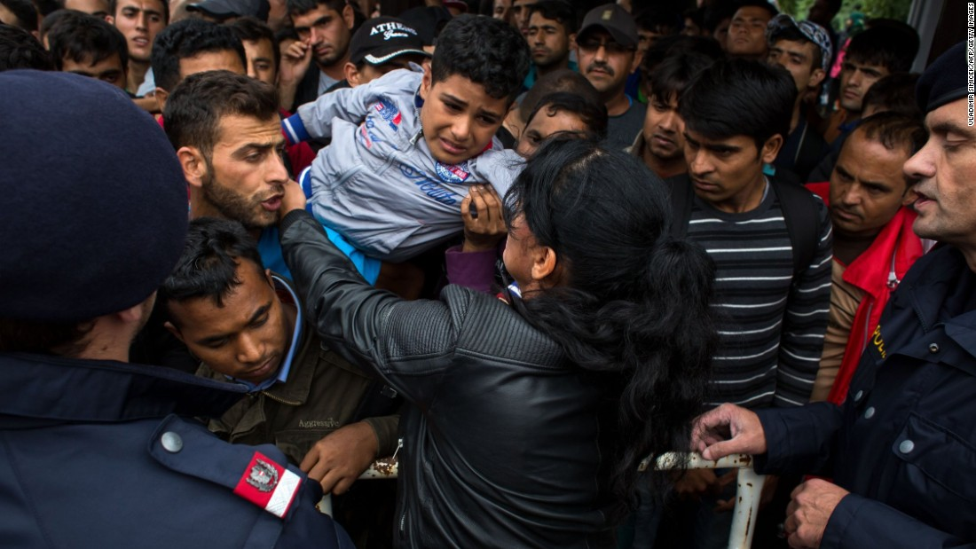 A woman holds a child as hundreds of migrants try to board a train in Nickelsdorf, Austria, on Saturday, September 5.