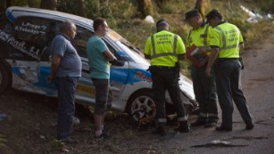Investigators stand beside a damaged rally car near the village of Carlal.