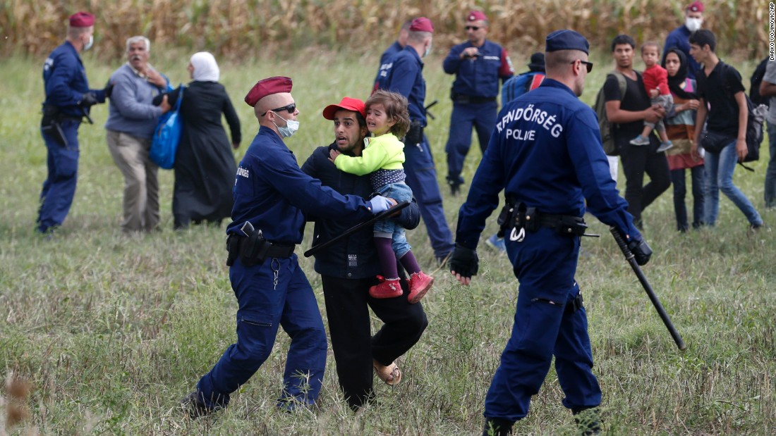 "Police officers stop people from leaving a cordoned-off area in Roszke, Hungary, on Tuesday, September 8. Many of the refugees and migrants arriving there from Serbia <a href=""http://www.cnn.com/2015/09/08/europe/migrant-crisis-hungary/index.html"" target=""_blank"">are afraid they will get stuck in Hungary</a> and be unable to carry on their journey to their preferred destinations in Western Europe, according to CNN's Arwa Damon."