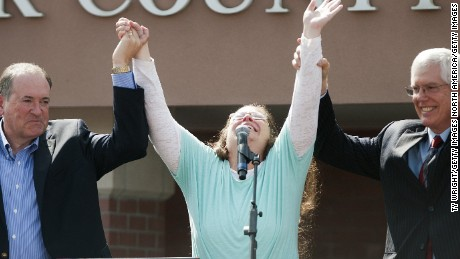 Rowan County Clerk of Courts Kim Davis holds her hands in the air with her attorney Mat Staver and Republican presidential candidate Mike Huckabee in front of the Carter County Detention Center on September 8, 2015 in Grayson, Kentucky.