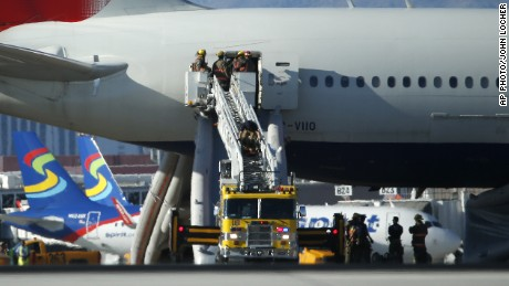 Firefighters stand outside the door of the British Airways plane that caught fire at McCarran International Airport in Las Vegas.