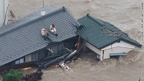 Local residents wait to be rescued on the roof of their home in a flooded area in Joso, Ibaraki Prefecture, on September 10, 2015. The Japanese city 50 km north east of Tokyo was flooded when Kinugawa river burst its banks, destroying homes and cars as desperate residents waited for help, and as thousands of people were ordered to evacuate. AFP PHOTO/Jiji Press      JAPAN OUT        (Photo credit should read JIJI PRESS/AFP/Getty Images)