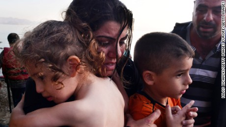 KOS, GREECE - AUGUST 15: A Syrian family arrives at a beach on the Greek island of Kos after crossing a part of the Aegean sea from Turkey to Greece in a dinghy on August 15, 2015 in Kos, Greece. The Greek government has sent a cruise ship to the island of Kos which will be able to house up to 2,500 refugees and operate as a registration centre, after 2,000 Syrian refugees were locked in an old stadium during a registration process and left without water for more than a day.  (Photo by Milos Bicanski/Getty Images)