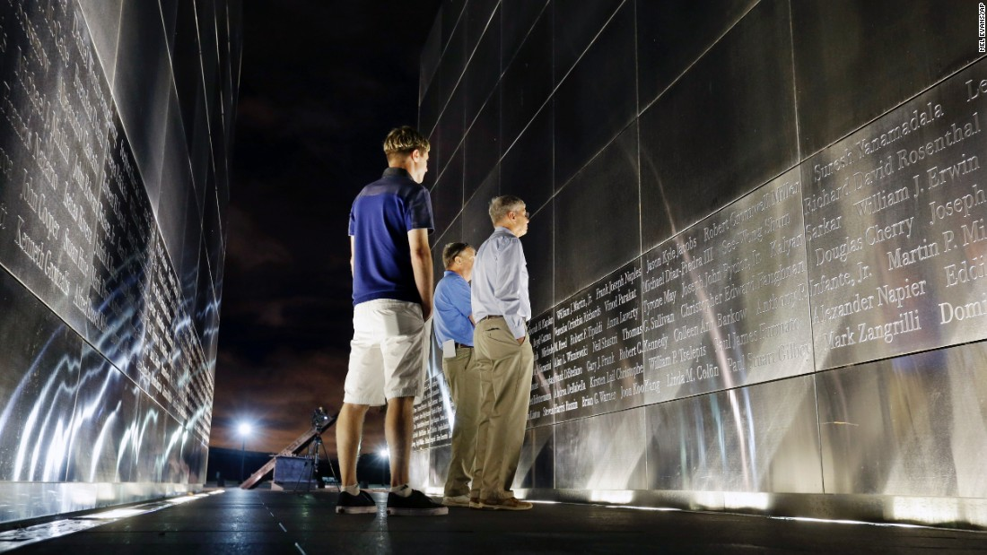 Terry Miller, right, and Chris Miller, center, look for the name of their brother Robert Cromwell Miller at the Empty Sky memorial to New Jersey's victims of 9/11. The memorial is in Jersey City across the Hudson River from the World Trade Center site. Nephew James Miller, left, joins them Friday.