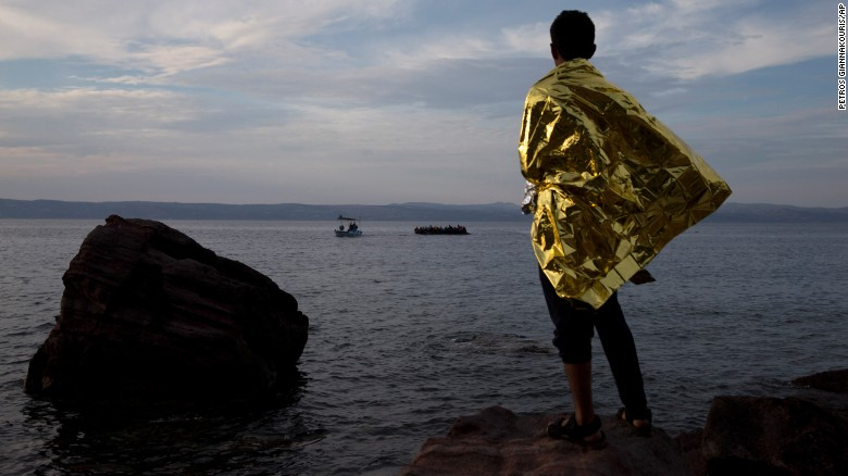 A refugee wrapped in a blanket watches a dinghy full of migrants approach the Greek island of Lesbos on Wednesday, September 9. More than 300,000 refugees and migrants heading to Europe have crossed the Mediterranean Sea so far in 2015, a U.N. spokeswoman says. Click through to see images from the refugee crisis in Europe.