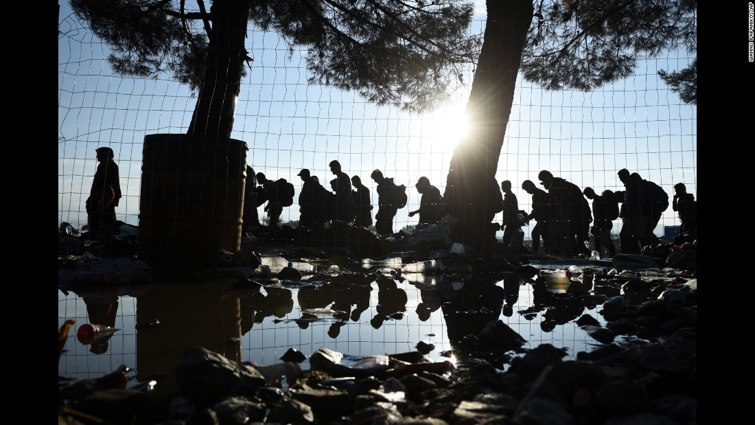 The sun rises as migrants walk from the northern Greek village of Idomeni to southern Macedonia on Friday, September 11.