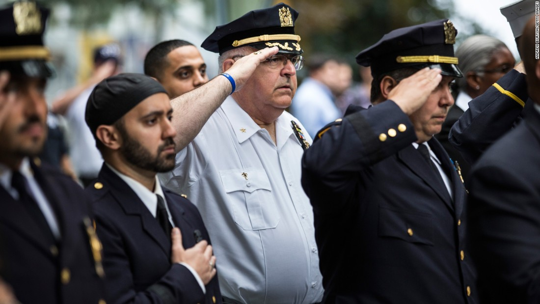 Law enforcement officials stand at attention Friday during the national anthem in an anniversary ceremony in New York in commemoration of the 9/11 attacks.