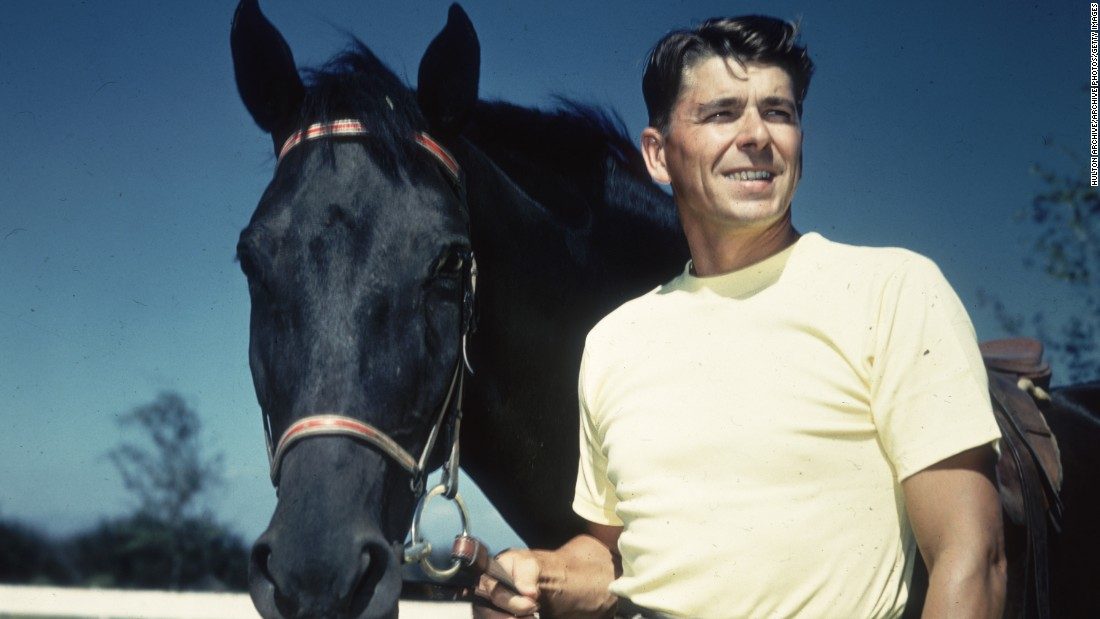 Reagan wears a T-shirt and stands next to a black horse in a 1935 portrait.