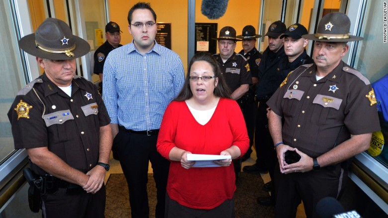 Surrounded by Rowan County Sheriff's deputies, Rowan County Clerk Kim Davis, center, with her son Nathan Davis standing by her side, makes a statement to the media at the front door of the Rowan County Judicial Center in Morehead, Ky., Monday, Sept. 14, 2015. Davis announced that her office will issue marriage licenses under order of a federal judge, but they will not have her name or office listed. (AP Photo/Timothy D. Easley)
