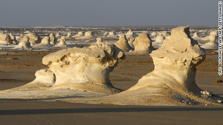 Rock formations called chalk Inselbergs glow as the sun sets in the Farafra Depression of south-western Egypt, 02 September 2007. Farafra, the home of the White desert with an estimated area of 1,800 square kilometres and lying 400 kilometres southwest of Cairo, is known worldwide for its unusual wind eroded rock formations. The Inselbergs found here are wind-carved eroded remnants of the Upper Cretaceous Era that are studied to understand similar formations found on other planets. More than 200 tourism-related personnel in this region are being educated about their preservation and to protect the fragile desert ecosystem. AFP PHOTO/CRIS BOURONCLE (Photo credit should read CRIS BOURONCLE/AFP/Getty Images)
