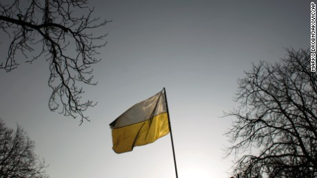 An ukrainian flag flies in central Kiev, Ukraine, Monday, Feb. 24, 2014. Ukraine's acting government issued a warrant Monday for the arrest of President Viktor Yanukovych, last reportedly seen in the pro-Russian Black Sea peninsula of Crimea, accusing him of mass crimes against protesters who stood up for months against his rule. (AP Photo/Marko Drobnjakovic)
