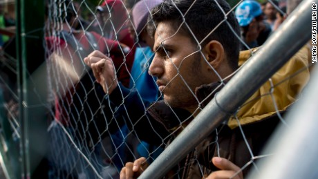 A migrant looks through a fence at the closed Roszke-Horgos border crossing at the border between Hungary and Serbia near Horgos, Serbia, Tuesday, Sept.15, 2015. (Tamas Soki/MTI via AP)