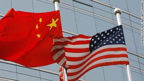 "Beijing, CHINA: A US and a Chinese flag wave outside a commercial building in Beijing, 09 July 2007. US Secretary of State Condoleezza Rice 06 July 2007 accused China of flouting the rules of global trade in its headlong economic expansion as the US administration ""has not been hesitant"" to deploy trade tools against China, including a complaint lodged with the World Trade Organization over copyright piracy. AFP PHOTO/TEH ENG KOON (Photo credit should read TEH ENG KOON/AFP/Getty Images)"