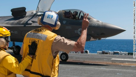 150526-N-BQ308-152 ATLANTIC OCEAN (May 26, 2015) Vice Adm. William Hilrides, commander of Naval Sea Systems Command, holds up two fingers to indicate to the F-35B Lightning II pilot to power up for takeoff aboard the amphibious assault ship the amphibious assault ship USS Wasp (LHD 1). Wasp, with Marine Strike Fighter Attack Squadron (VMFA) 121 and VMFAT-501 embarked, is underway conducting the first phase of operational testing for the F-35B aircraft, which will evaluate the full spectrum of F-35B measures of suitability and effectiveness in an at-sea environment. (U.S. Navy photo by Chief Mass Communication Specialist William Tonacchio/Released)