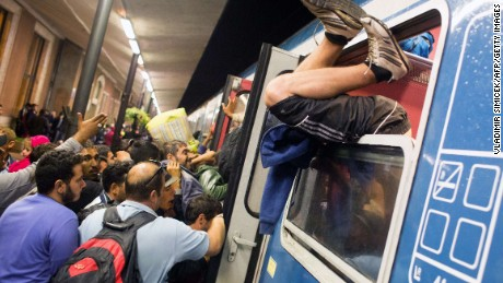 A man climbs through the window as refugees struggle to get on a train from Gyor to Hegyeshalom in Hungary on September 19, 2015.