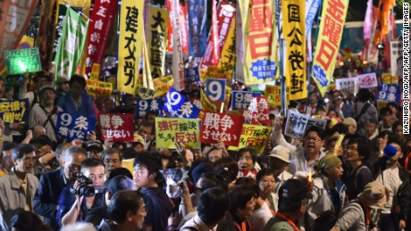 Demonstrators stage a rally against Japanese Prime Minister Shinzo Abe's controversial security bills in front of the National Diet in Tokyo on September 18, 2015.  Japan was expected to pass security bills on September 18 that would allow troops to fight on foreign soil for the first time since World War II, despite fierce criticism it will fundamentally alter the character of the pacifist nation.   AFP PHOTO / KAZUHIRO NOGI