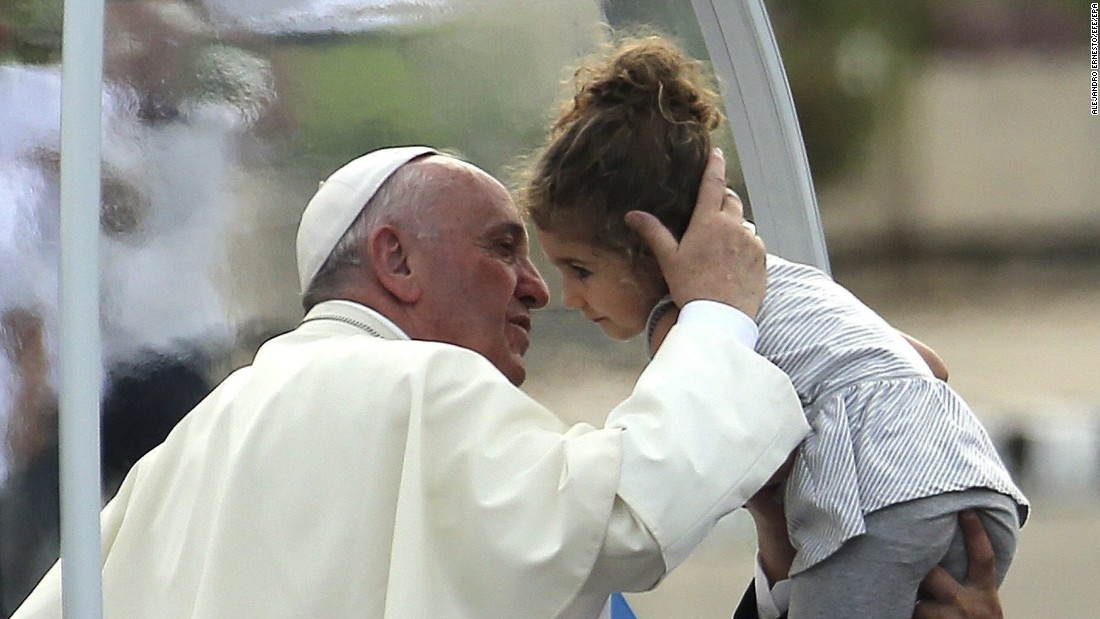 Pope Francis kisses a child as he arrives in Revolution Square on September 20.