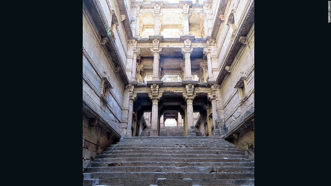 """""""This impressive, ignored, disintegrating stepwell is in a small village about 15 minutes away from its famous sister, Rudabai vav in Adalaj, and yet no-one ever visits. It was built at the same time, most likely by the same queen, and while less showy and grand it's nevertheless beautiful and elegant, with sculptural niches climbing up the narrow walls. It's """"protected"""" by the local government (even though chunks are falling from it and bonfires have been lit within) but easily accessible through an adjacent temple."""""""