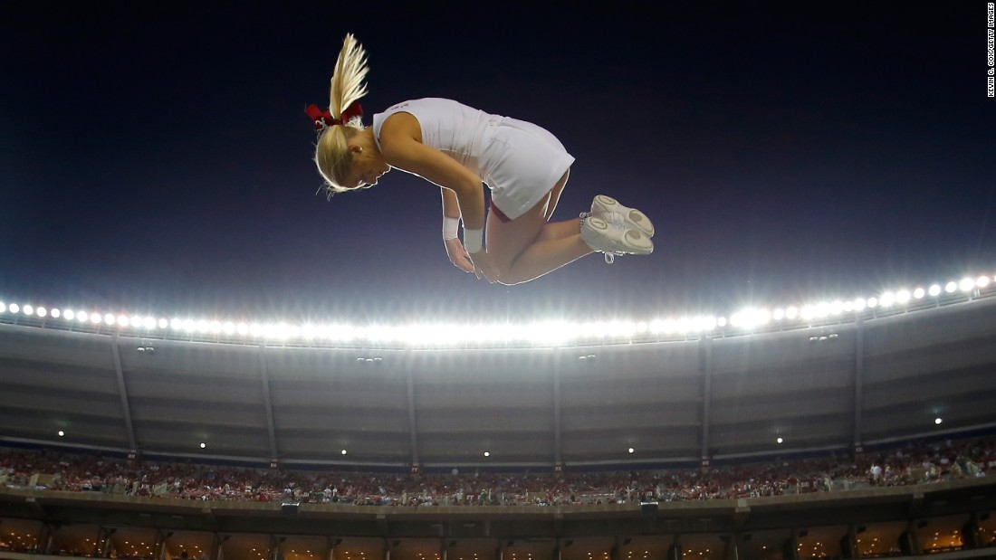 An Alabama cheerleader is tossed into the air prior to a college football game in Tuscaloosa, Alabama, on Saturday, September 19.