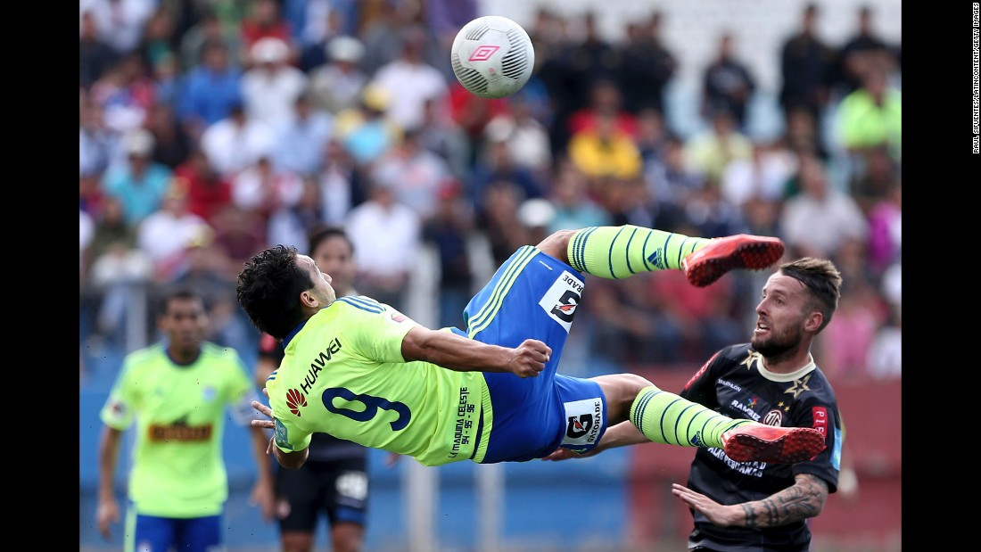 Sporting Cristal's Cesar Pereyra goes horizontal as he tries to kick a ball Wednesday, September 16, in Cajamarca, Peru.