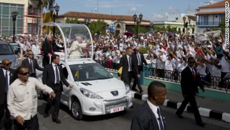 "Security surrounds Pope Francis' popemobile as he greets residents as he makes his way to the Metropolitan Cathedral to celebrate Mass in Santiago de Cuba, Cuba, Tuesday, Sept. 22, 2015. Pope Francis on Tuesday called on Cubans to rediscover their Catholic heritage and live a ""revolution of tenderness,"" powerful words in a country whose 1959 revolution installed an atheist, communist government that sought to replace the church as the guiding force in people's lives. (AP Photo/Eduardo Verdugo)"