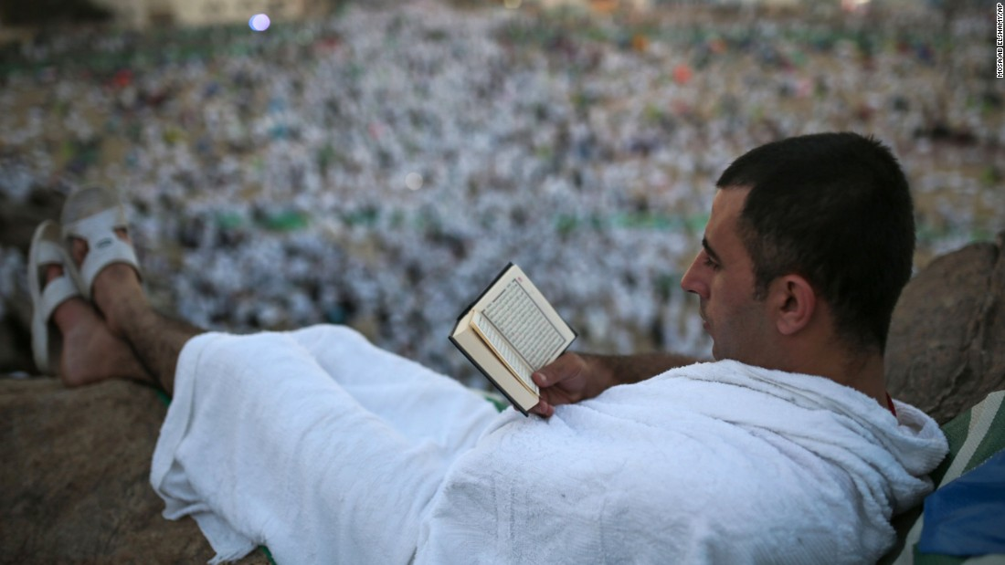 A pilgrim reads the Quran on a rocky hill called the Mountain of Mercy, on the plain of Arafat, near Mecca on Wednesday, September 23.