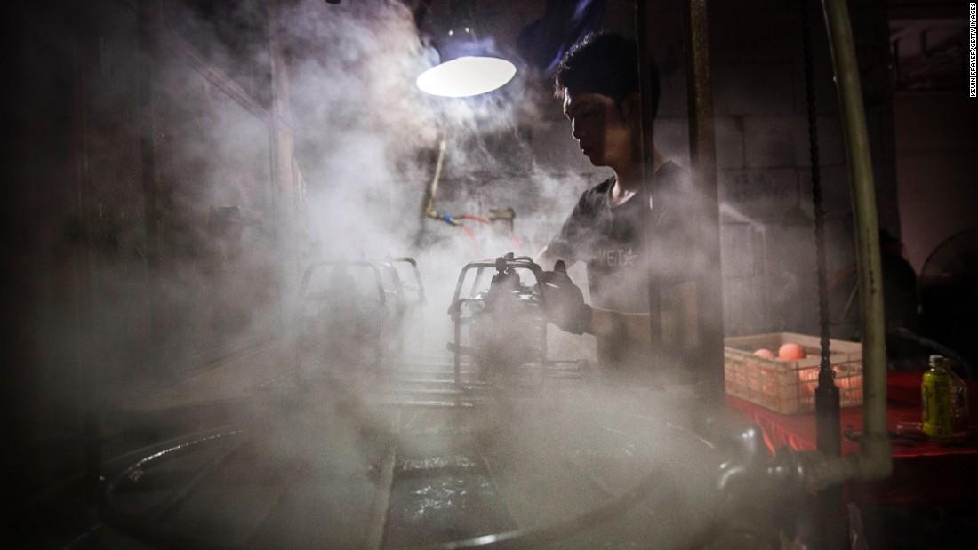 Ένας Κινέζος εργάτης δροσίζει πλαστική κούκλα κεφάλια στο νερό, αφού έγιναν σε φούρνο σε ένα εργοστάσιο παιχνιδιών στις 17 Σεπτεμβρίου στο Xitang.  Euromonitor προβλέπει ότι μέσα στα επόμενα πέντε χρόνια, η Κίνα θα είναι η ταχύτερα αναπτυσσόμενη αγορά παγκοσμίως για τα παραδοσιακά παιχνίδια και τα παιχνίδια.  Λένε ότι η αγορά θα αυξηθεί στο 57% μέχρι το 2018.